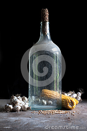 Old bottle of alcohol with maize, corn and garlic