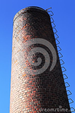Old brick chimney on blue sky