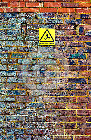 Old brick wall with warning sign