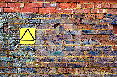 Old brick wall with yellow sign