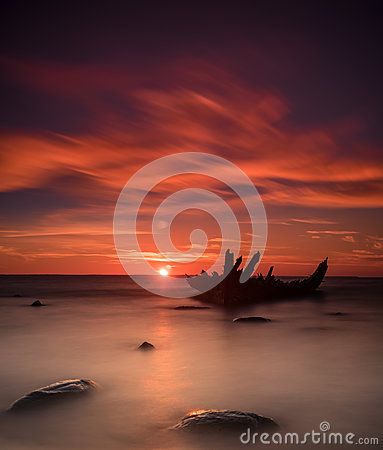 Free Old Broken Boat Wreck On The Shore, A Frozen Sea And Beautiful Blue Sunset Background. Royalty Free Stock Images - 83472309