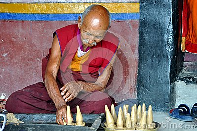 Old Buddhist monk preparing butter sculptures Editorial Stock Photo