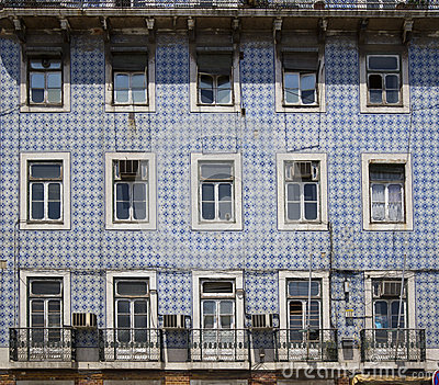 Old building with tiled facade and damaged windows