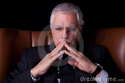 Old businessman  seated on a chair, thinking