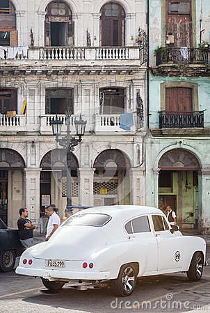 Old car next to crumbling buildings in Havana Editorial Image