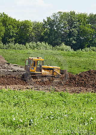 Old caterpillar tractor works in fields