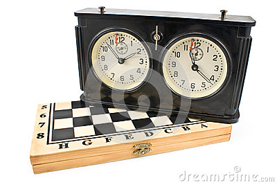 Old chess clock on chessboard