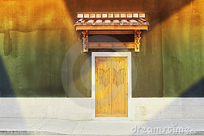 An old chinese  door  in a illuminating wall