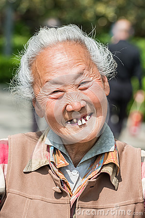 Old chinese woman friendly toothless toothy smiling outddors por Editorial Stock Image