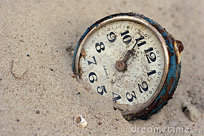 An old clock in the sand