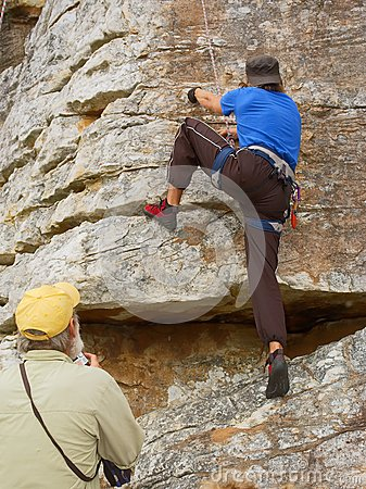 Old coach looks at rock climber