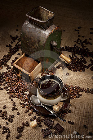 Old coffee mill and cup of coffee