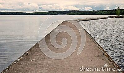 Old concrete pier on calm lake in Finland