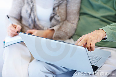 Old couple extracting data from laptop