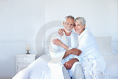 An old couple having fun together in the bedroom