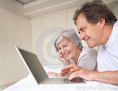 Old couple lying on the bed while using a laptop