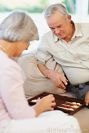 An old couple playing a game of backgammon