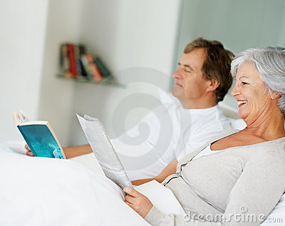 Old couple reading magazine while lying on bed