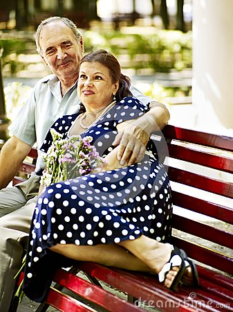 Old couple sit on bench.
