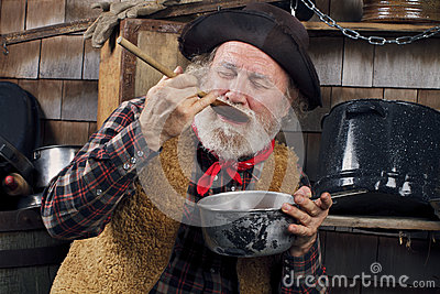 Old Cowboy Cook Tasting Food From Outdoor Kitchen Royalty Free Stock Image - Image: 26845576