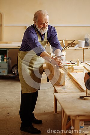 Free Old Craftsperson Is Working With Building Materials Royalty Free Stock Images - 118743689