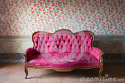 Old damaged red couch in an antique house. Flowers wallpaper in the wall