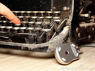 Old dark typewriter with modern mouse