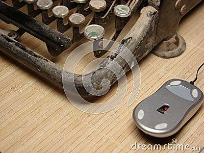 Old dark typewriter with modern mouse