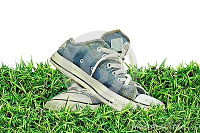 Old, dirty sneakers over spring green grass