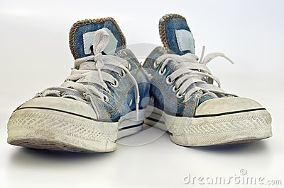 Old, dirty sneakers over white background