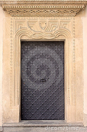 Old door with ornament in stone wall