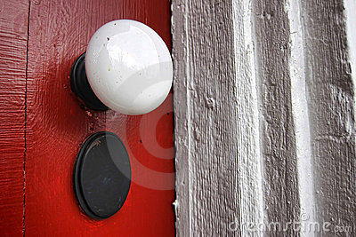 Old Doorknob on Antique Red Door of Historic Home