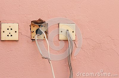 Old electricity socket and wires on cement wall with copy space for text and design art work Stock Photo