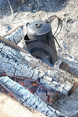 An old fashioned coffee pot on an open fire