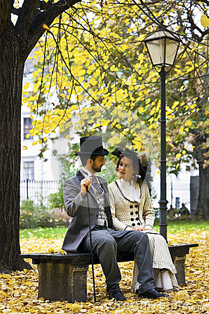 Free Old-fashioned Dressed Couple On A Park Bench In Fall. Stock Images - 32290434