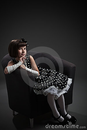Old-fashioned dressed little girl sitting on chair
