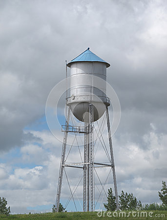 Old fashioned water tower on a hill.
