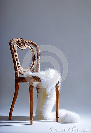 Old-fashioned wooden chair with white fur
