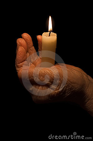Old female hands with a candle