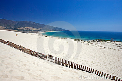 Old fence sticking out of deserted sandy beach dunes
