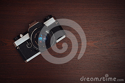 Old film camera on a wooden table