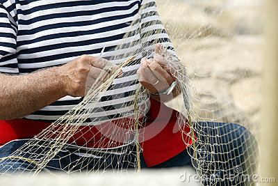 Old fisherman Mending Nets