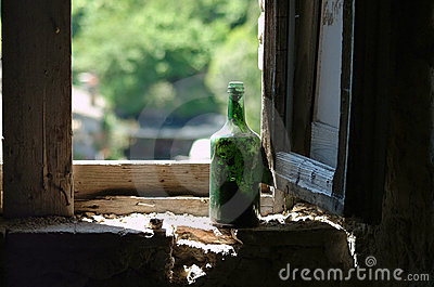 Old green wine bottle in window
