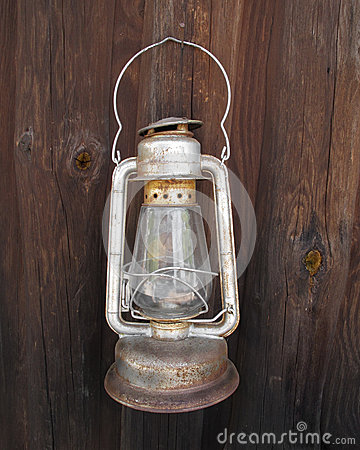 Old hanging kerosene lantern on wall.