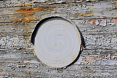 Old iron porthole on wooden