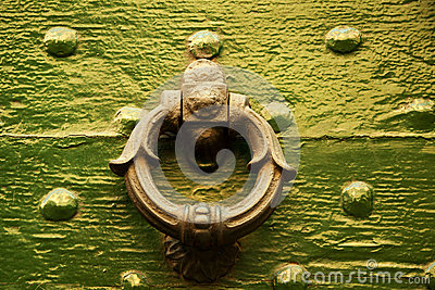 Old Italian round shape door knocker on green wood