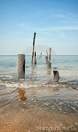Old jetty pillars in sea