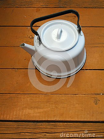 Old kettle on the wooden floor
