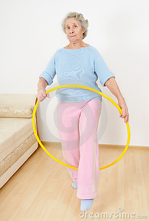 Old lady doing gymnastic with hula-hoop