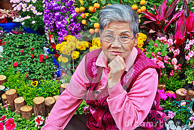 Old lady in front of Flower garden